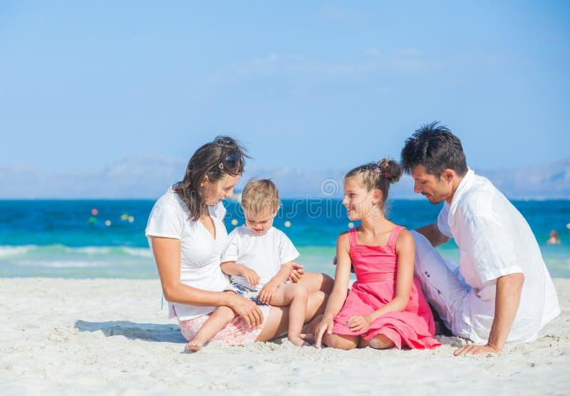 Agregado familiar com quatro membros na praia tropical fotografia de stock