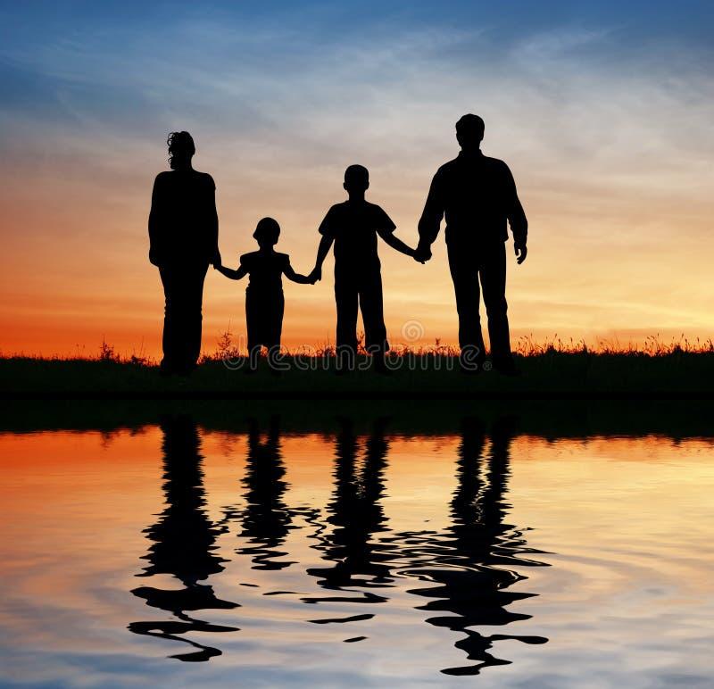 Agregado familiar com quatro membros no céu do por do sol imagem de stock royalty free