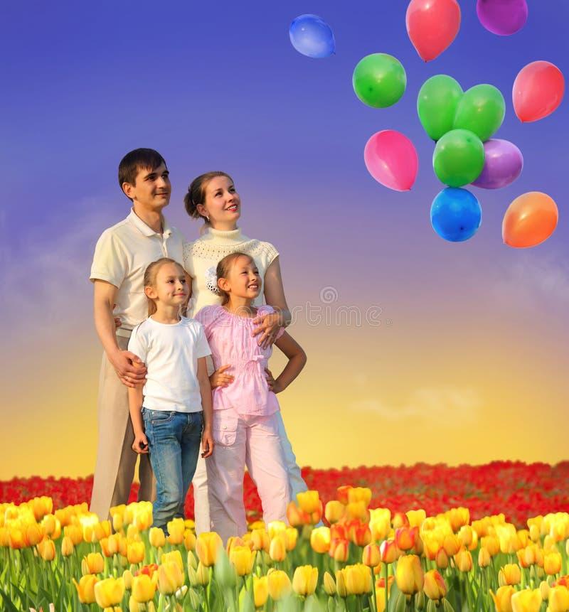 Agregado familiar com quatro membros no campo do tulip e na colagem dos balões foto de stock