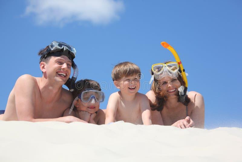 Agregado familiar com quatro membros que encontra-se com máscaras snorkeling fotografia de stock