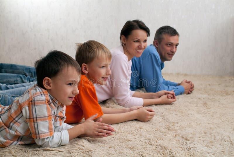 Agregado familiar com quatro membros que encontra-se no tapete fotos de stock royalty free