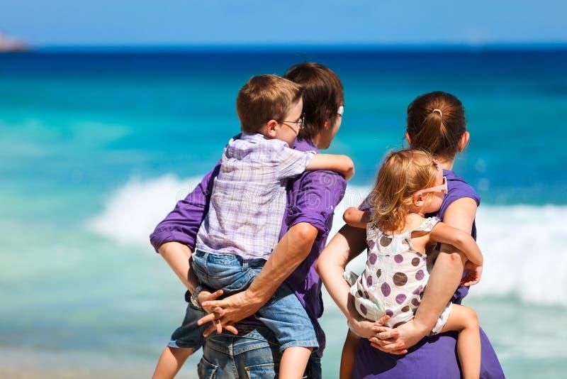 Agregado familiar com quatro membros que olha ao oceano fotos de stock