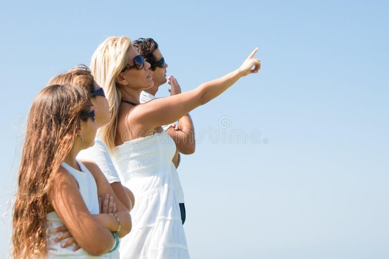 Agregado familiar com quatro membros que olha o céu fotografia de stock
