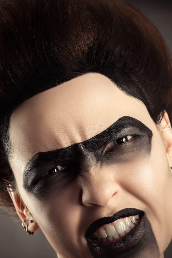Agressief vrouwengezicht met creatieve donkere make-up royalty-vrije stock fotografie