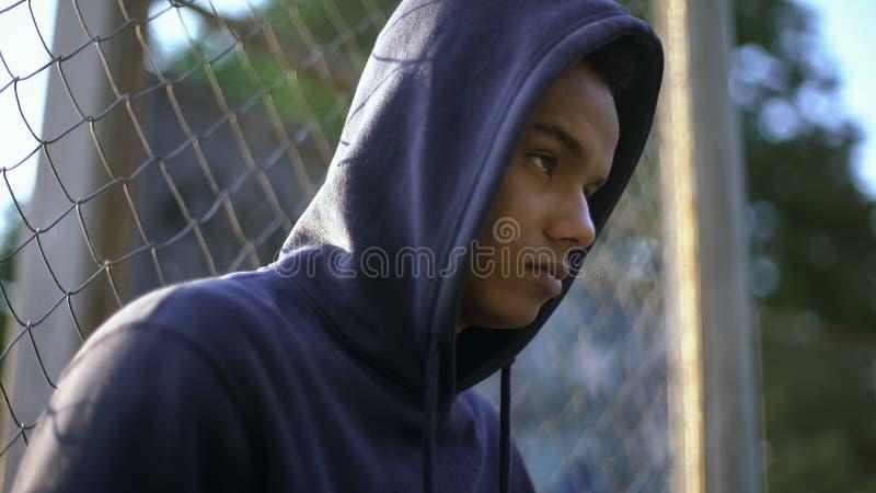 Agressieve Afro-Amerikaanse tiener klaar om misdaad, gebrek aan juiste opvoeding te begaan stock foto
