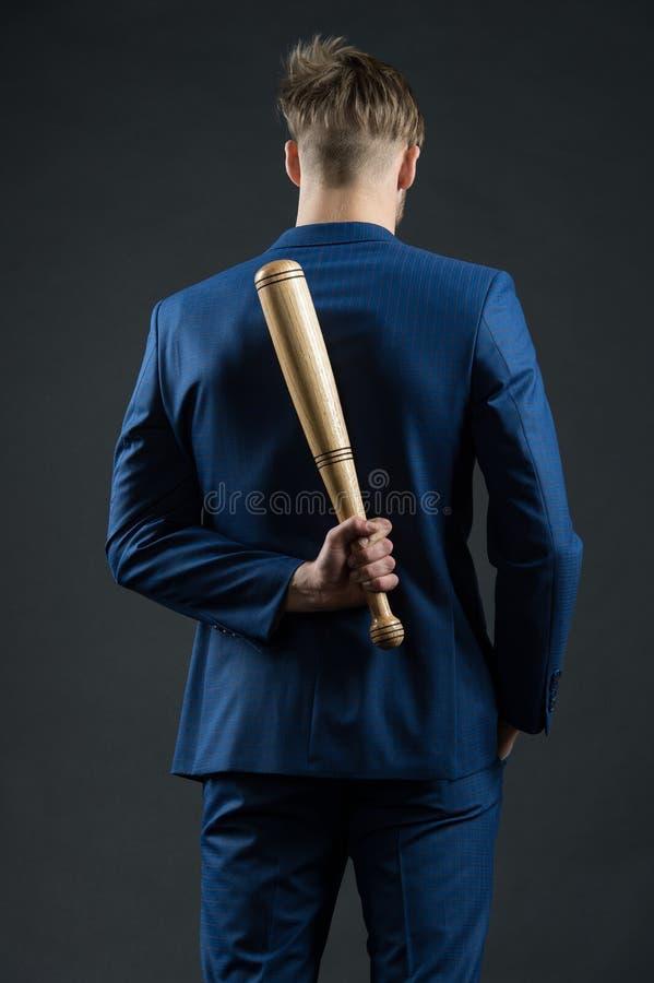 Agression latente L'homme d'affaires ou l'homme dans le costume formel cache le dos de batte en bois derrière, fond foncé Danger  image libre de droits