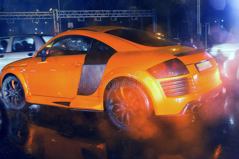 Agressive and brutal orange sport car on rained road picture useful for background stock image