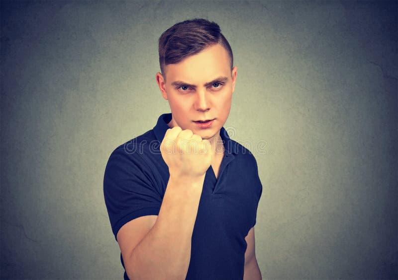 Agresywny młodego człowieka grożenie z pięści ręką zdjęcie stock