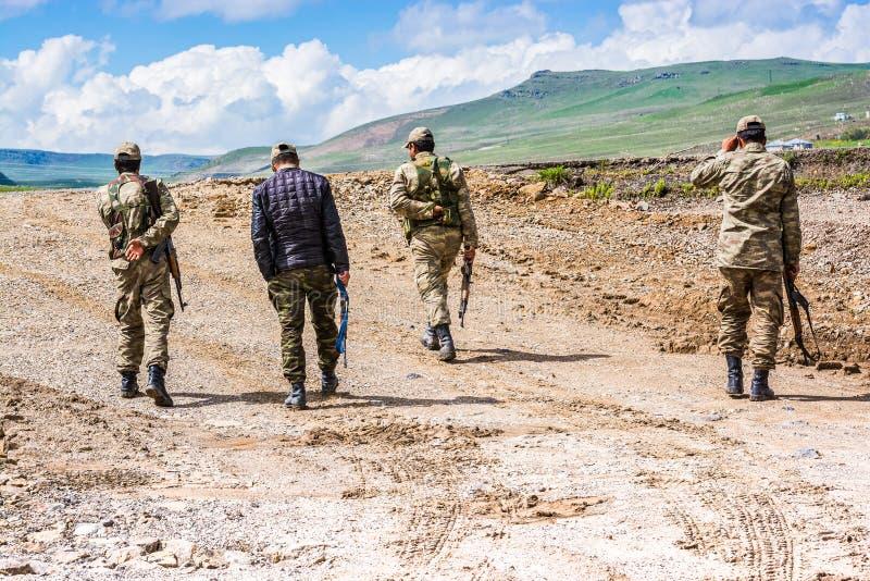 Agri Turkiet - Maj 24, 2017 Turkiska soldater som går på den leriga vägen royaltyfri foto