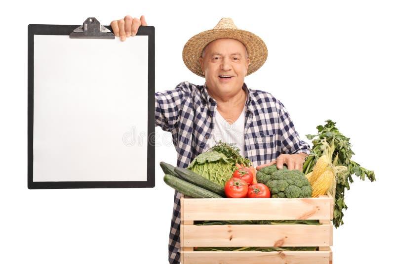 Agricoltore anziano allegro che tiene una lavagna per appunti immagini stock libere da diritti