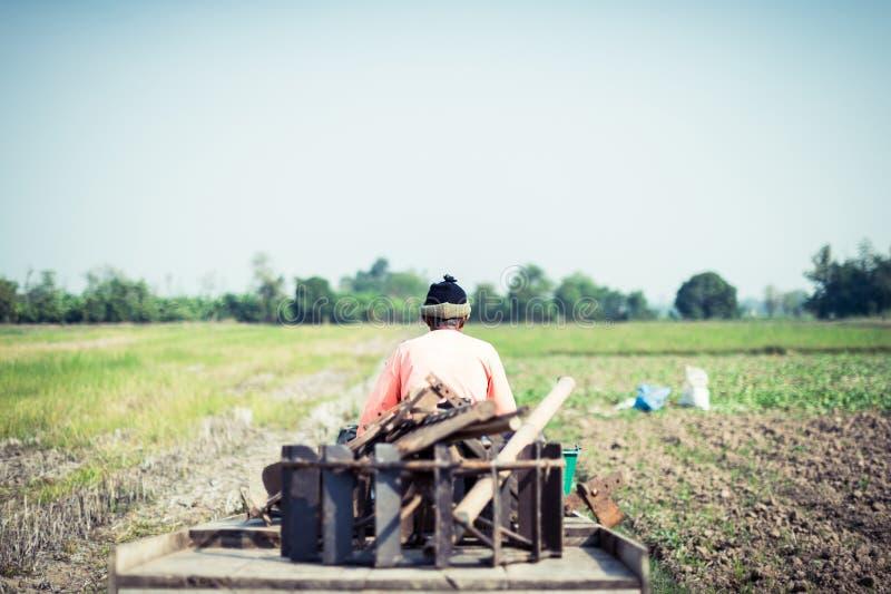 Agricoltore che guida trattore in un'azienda agricola fotografia stock