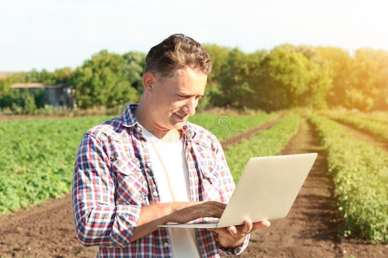 Agricoltore che per mezzo del computer portatile immagini stock libere da diritti