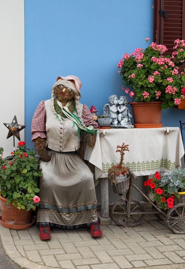 Agricoltore che si siede davanti ad una fattoria, vacanze di Pasqua, decorazioni di signora della bambola della paglia in Austria fotografia stock