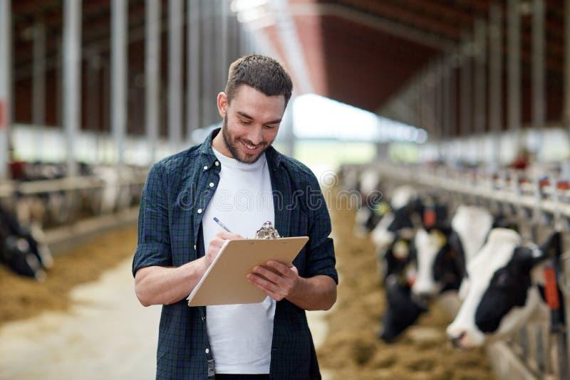 Agricoltore con la lavagna per appunti e le mucche in stalla sull'azienda agricola fotografia stock libera da diritti