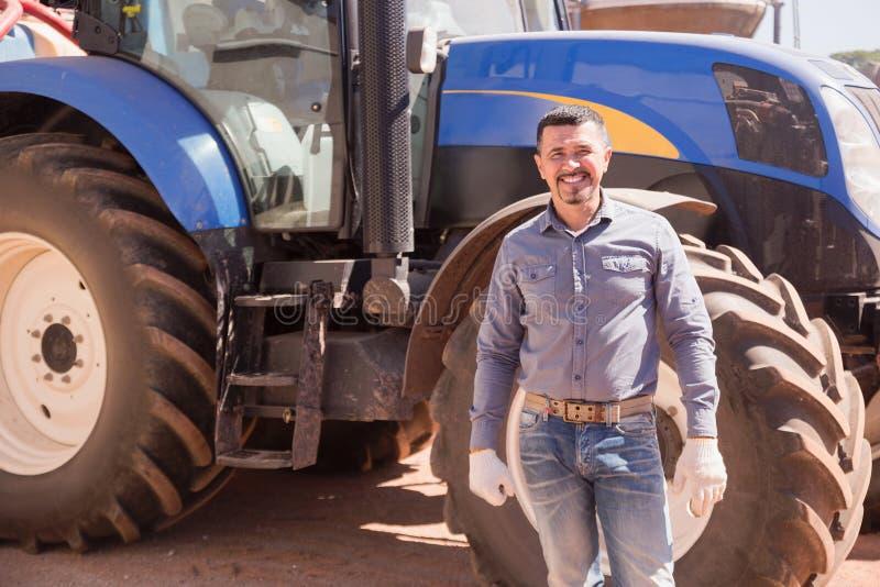 Agricoltore felice del driver che sta con il grande trattore immagini stock libere da diritti
