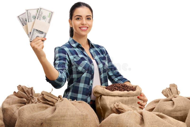 Agricoltore femminile con il mucchio dei sacchi della tela da imballaggio e dei pacchi dei soldi fotografia stock