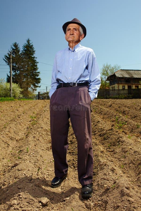 Agricoltore senior che sta all'aperto fotografia stock