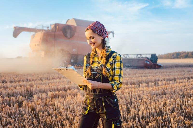 Agricoltore su un campo durante il raccolto con la lavagna per appunti immagini stock libere da diritti
