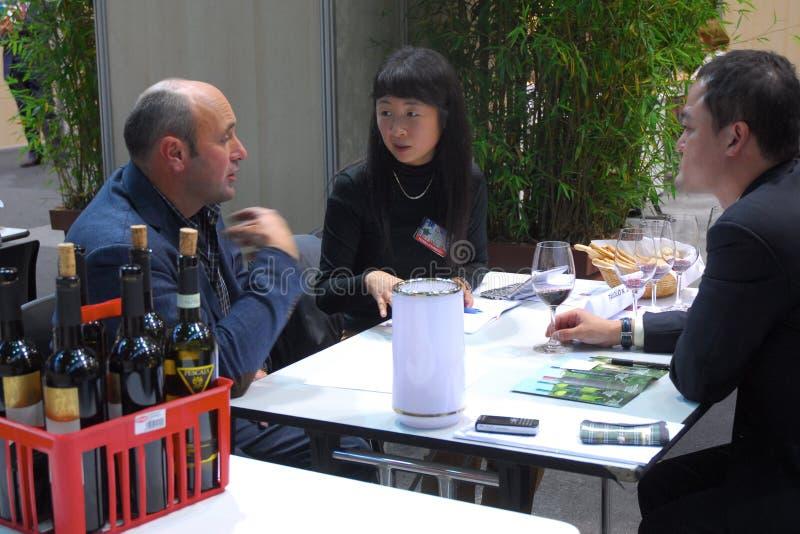 Agricoltori della fiera di commercio del vino allo scrittorio con gli importatori ed i distributori commerciali mondiali fotografie stock libere da diritti