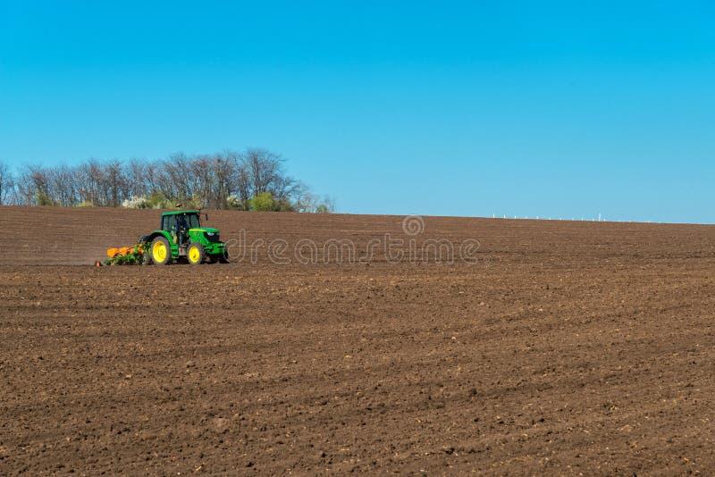 Agriculteur avec l'ensemencement de tracteur - l'encemencement cultive au champ agricole image stock
