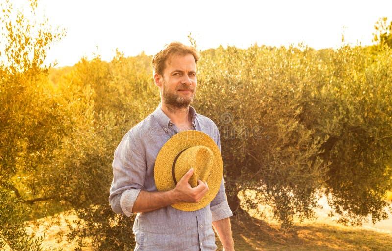 Agriculteur avec le chapeau de paille devant un verger olive - agriculture photo libre de droits