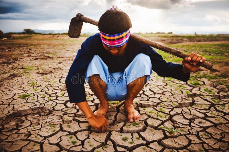 Agriculteur désespéré et seul sitiing sur la terre sèche et trouvant les plantes vivantes Crise de réchauffement global photographie stock