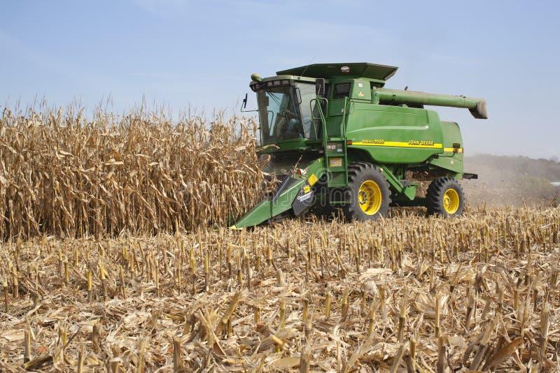 Agriculteur dans un maïs de récolte mécanisée de John Deere images stock