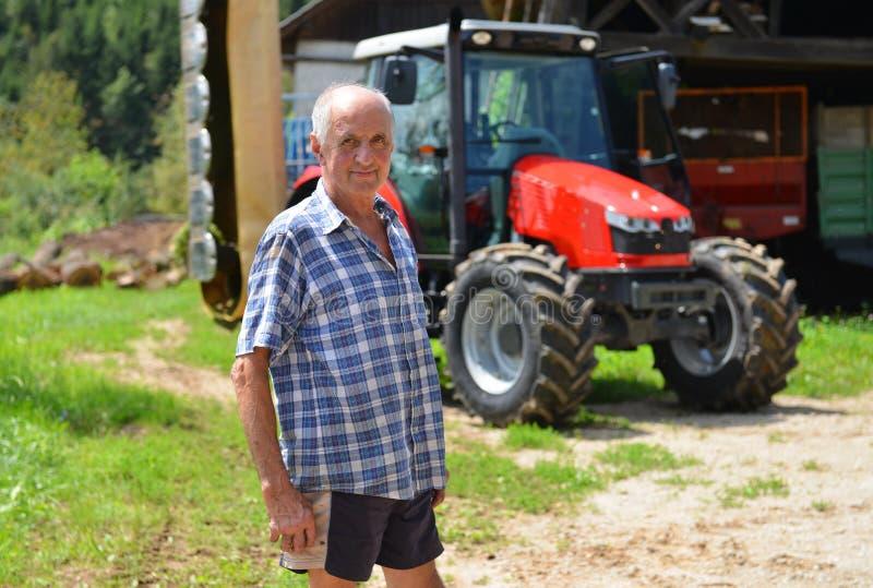 Agriculteur fier se tenant devant son tracteur image libre de droits