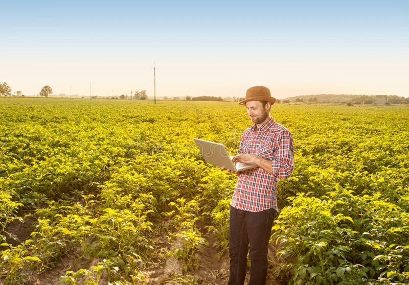 Agriculteur heureux avec l'ordinateur portable devant le champ photos stock
