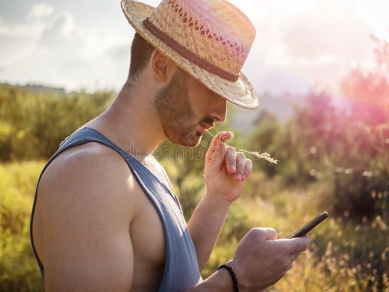 Agriculteur masculin bel extérieur avec le téléphone portable photos stock