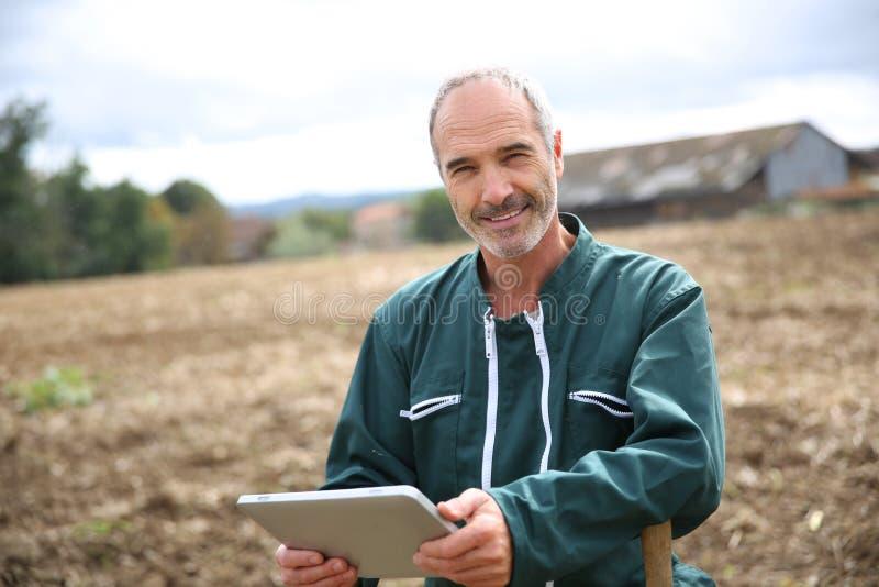 Agriculteur moderne se tenant dans le domaine avec le comprimé photographie stock