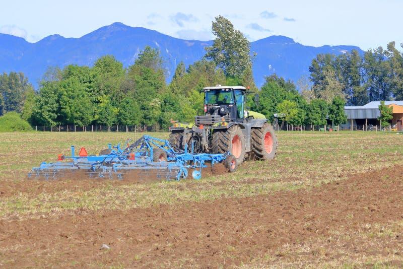 Agriculteur Plows Field pour l'ensemencement de ressort image stock