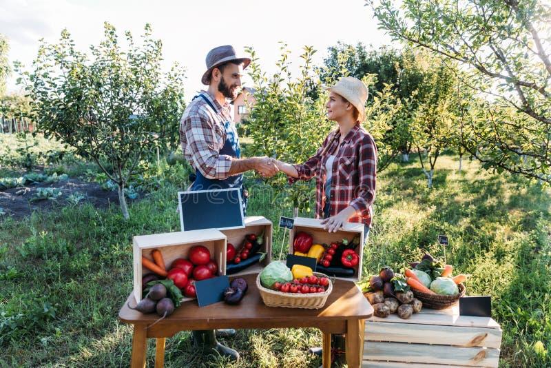 Agriculteurs se serrant la main au marché photos stock