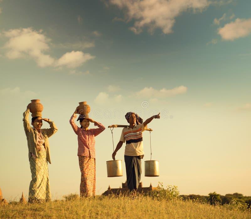 Agriculteurs traditionnels birmans asiatiques de groupe dans le coucher du soleil image stock
