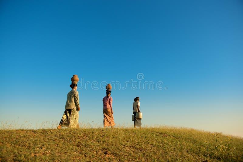 Agriculteurs traditionnels birmans asiatiques de groupe marchant à la maison photos stock