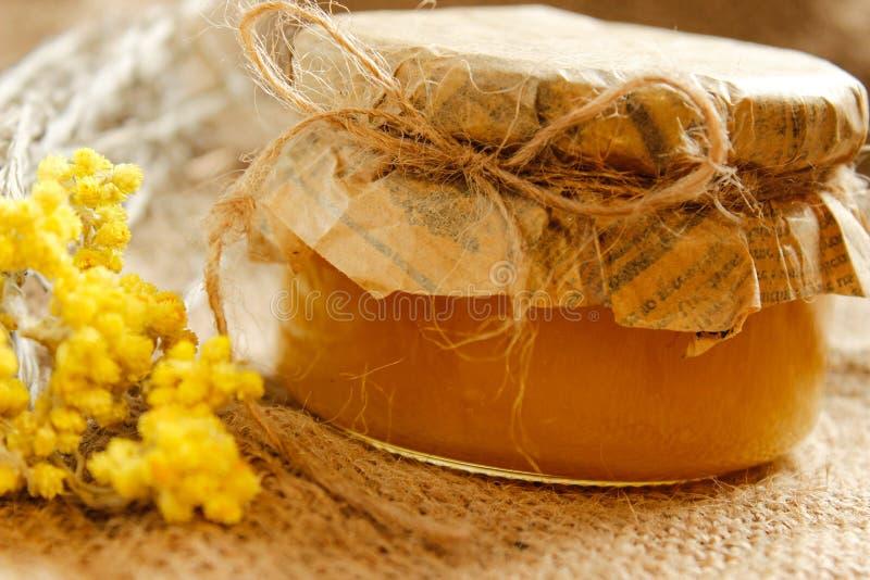 agricultura Deposite com mel com as flores secas amarelas na serapilheira Vista lateral fotografia de stock royalty free