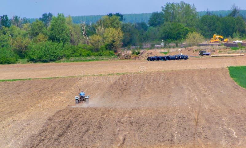 Agricultura, trator que prepara a terra com cultivador da sementeira imagens de stock royalty free