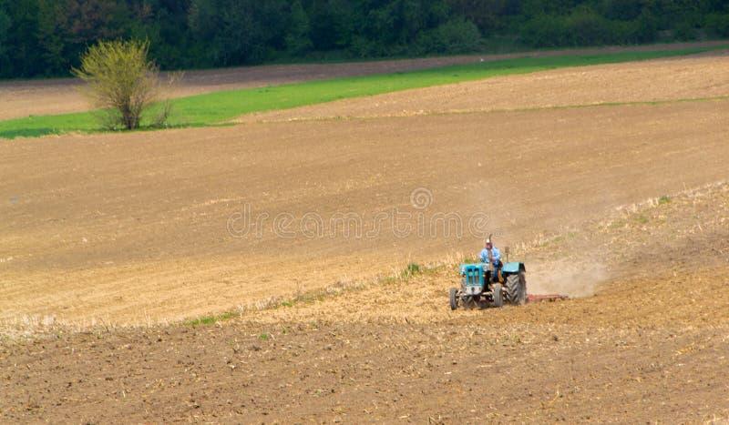 Agricultura, trator que prepara a terra com cultivador da sementeira fotografia de stock