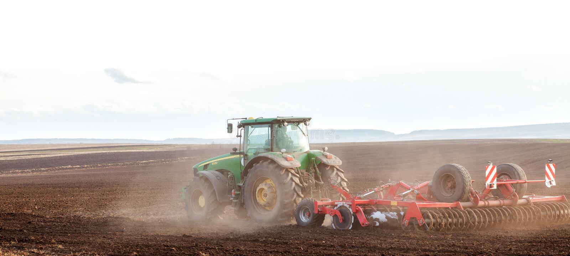 Agricultura, trator que prepara a terra com o cultivador da sementeira como parte das atividades pre de semeação na estação de mo fotografia de stock royalty free