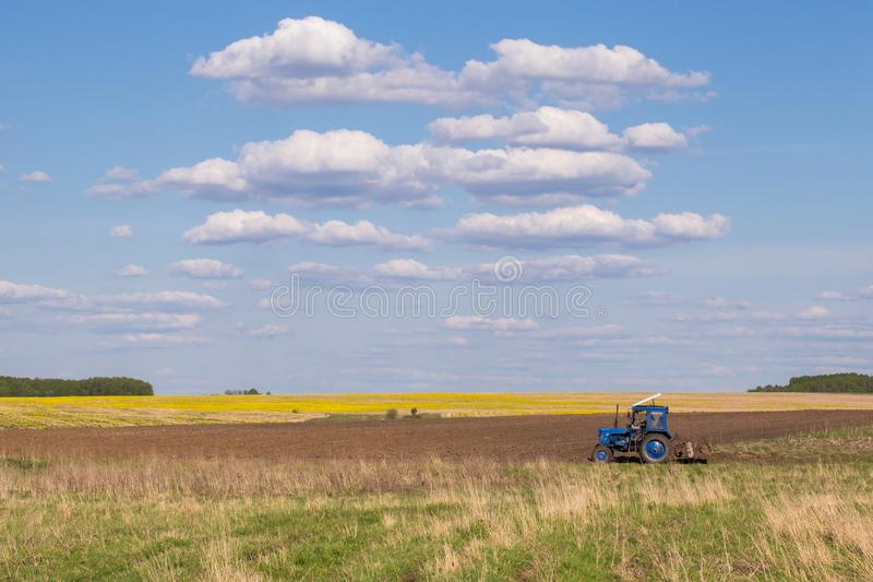 Agricultural farm field. Tractor cultivating stock image