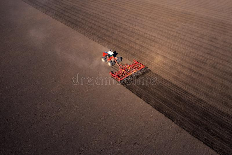 Agricultural industrial tractor plows soil field for sowing , aerial top view. Land cultivation, spring farming concept royalty free stock images