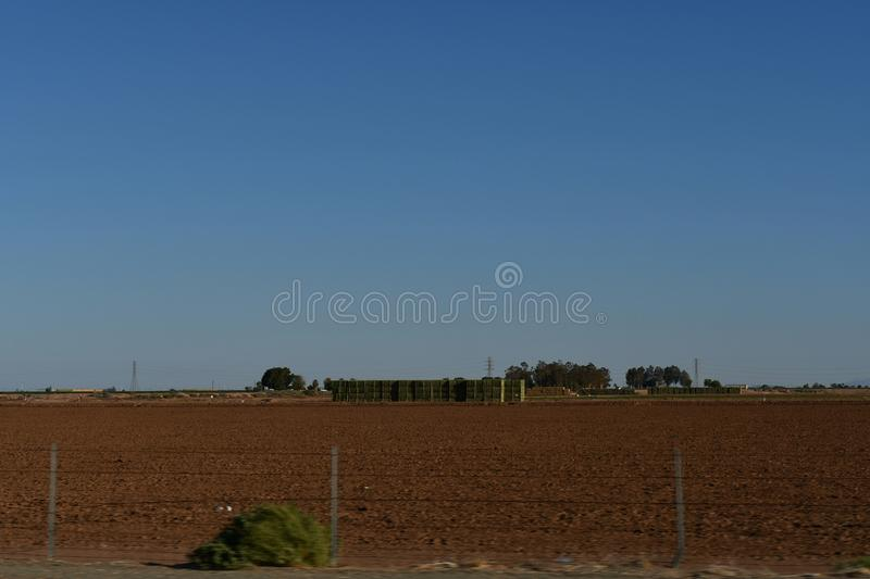 El Centro farm field with mountains. Agricultural landscape of a farm field with mountains in the background. El Centro California. Imperial Valley farms royalty free stock images