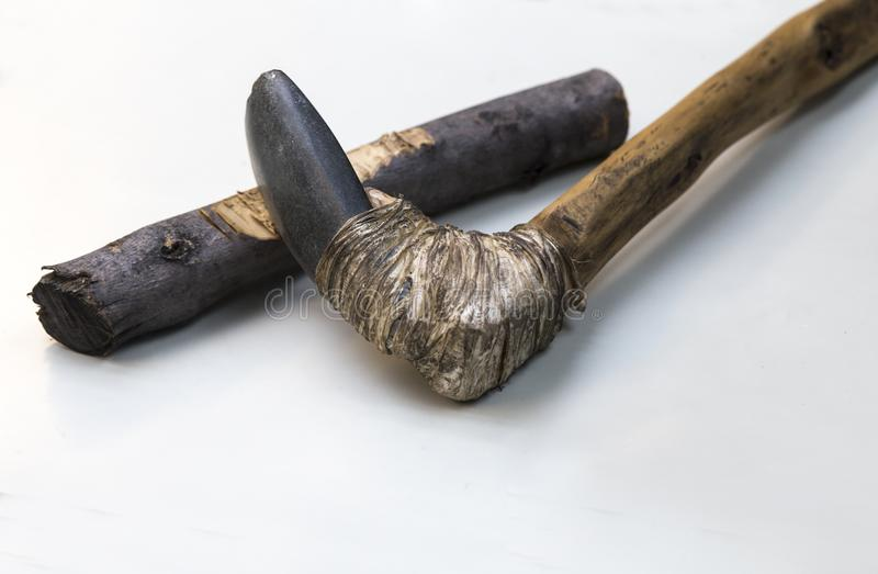 Agricultural lithic tool with wooden handle assembled with tendon. Agricultural lithic tool with wooden handle joint with tendon. Replica, Isolated over white royalty free stock photo
