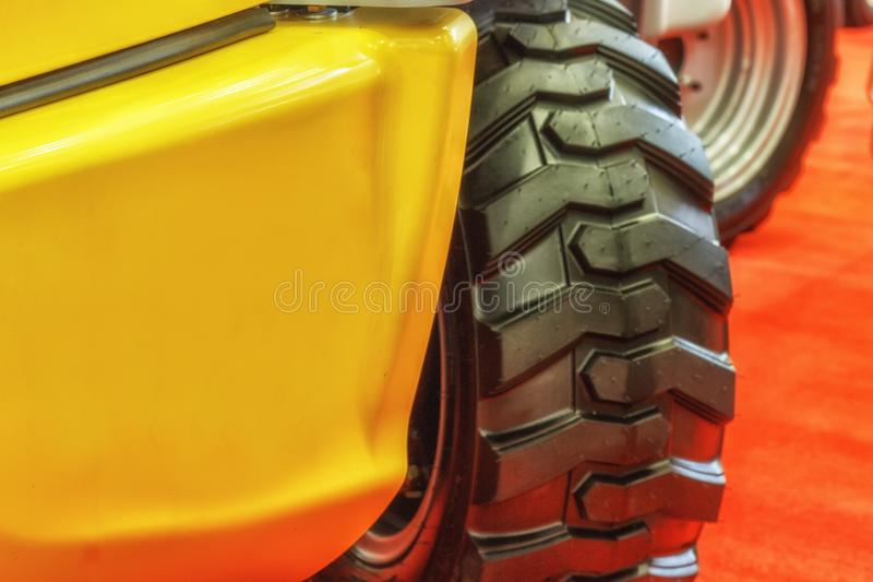 Agricultural machinery. Front wheel of a yellow tractor royalty free stock image