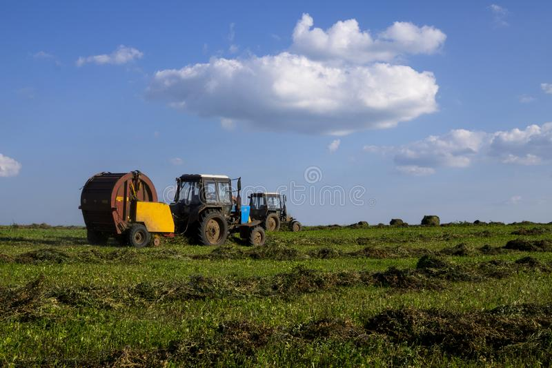 Agricultural machinery, a tractor collecting grass in a field against a blue sky. Hay harvesting, grass harvesting. Season. Harvesting, grass, agricultural land royalty free stock image