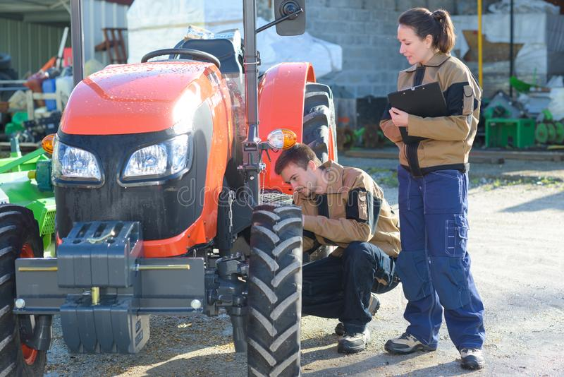 Agricultural mechanics checking tractors condition before harvesting. Mechanic royalty free stock images