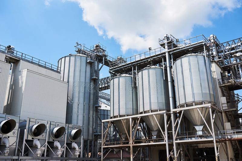 Agricultural Silos. Building Exterior. Storage and drying of grains, wheat, corn, soy, sunflower against the blue sky royalty free stock photos