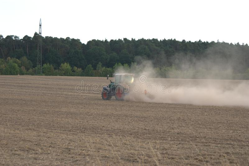 Agricultural tractor harrowing a field during the summer drought of 2018 in Germany. Agricultural tractor with a harrow attachment, plowing up a field during the stock photo