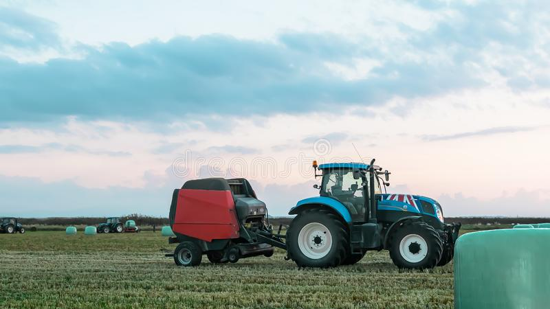 Agricultural work in a field at sunset. Equipment for forage. Film wrapping system. Round bales of feed for farm animals.  royalty free stock photography