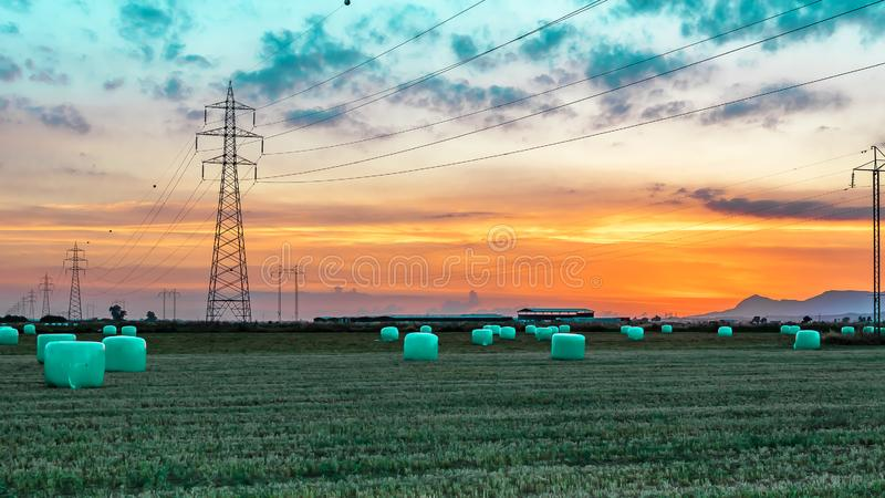 Agricultural work in a field at sunset. Equipment for forage. Film wrapping system. Round bales of feed for farm animals.  stock photography